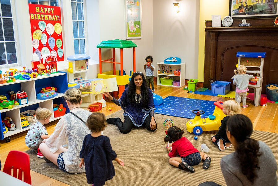 Children in a colourful nursery looking towards a woman reading a book