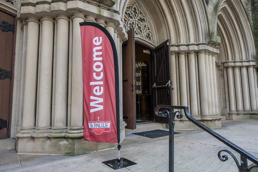 Red welcome banner outside the doors of a church